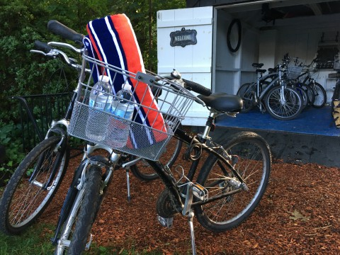 a photo of two bicycles with baskets that contain water bottles. they are in front of a shed full of bicycles