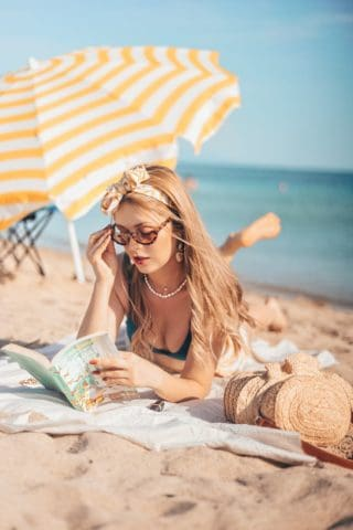 a woman reading a book on the beach