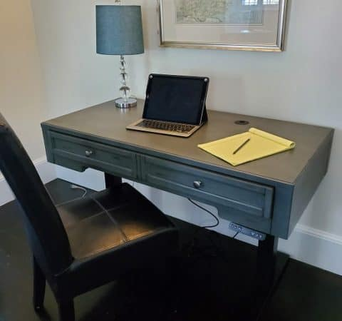 a photo of a chair and a desk with a laptop, table lamp, and notepad