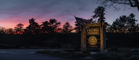 the truro vineyards sign in front of a sunset